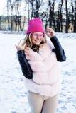 Muchacha bastante adolescente del inconformista de los jóvenes al aire libre en el parque de la nieve del invierno que come el ca Foto de archivo libre de regalías