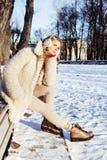 Muchacha bastante adolescente del inconformista de los jóvenes al aire libre en el parque de la nieve del invierno que come el ca Fotografía de archivo