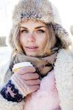 Muchacha bastante adolescente del inconformista de los jóvenes al aire libre en el parque de la nieve del invierno que come el ca Fotos de archivo
