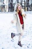 Muchacha bastante adolescente del inconformista de los jóvenes al aire libre en el parque de la nieve del invierno que come el ca Foto de archivo