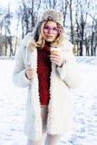 Muchacha bastante adolescente del inconformista de los jóvenes al aire libre en el parque de la nieve del invierno que come el ca Imagen de archivo