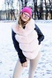 Muchacha bastante adolescente del inconformista de los jóvenes al aire libre en el parque de la nieve del invierno que come el ca Imagenes de archivo