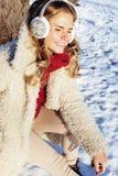 Muchacha bastante adolescente del inconformista de los jóvenes al aire libre en el parque de la nieve del invierno que come el ca Fotografía de archivo libre de regalías