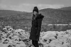 Muchacha bastante adolescente en la nieve, haciendo frente a la cámara, blanco y negro Imagen de archivo libre de regalías
