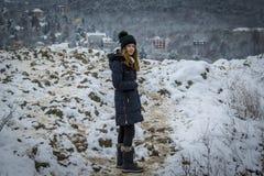 Muchacha bastante adolescente en la nieve, haciendo frente a la cámara, tema del invierno Imagen de archivo