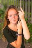 Muchacha bastante adolescente que balancea en un cuerda-oscilación en el campo Fotos de archivo
