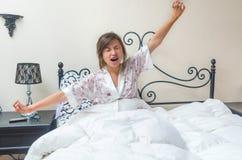 Muchacha bastante adolescente que despierta en cama Foto de archivo libre de regalías