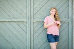Muchacha bastante adolescente que escucha la música en su dispositivo Imagen de archivo libre de regalías