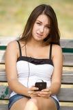 Muchacha bastante adolescente que escucha la música en su móvil Imagenes de archivo