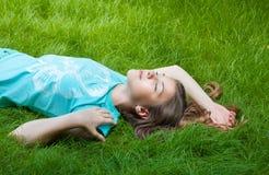 muchacha bastante adolescente que miente en la hierba risa, alegría, emociones positivas Imagen de archivo
