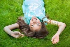 muchacha bastante adolescente que miente en la hierba risa, alegría, emociones positivas Fotos de archivo