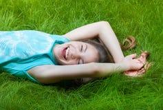 muchacha bastante adolescente que miente en la hierba risa, alegría, emociones positivas Fotografía de archivo