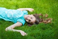 muchacha bastante adolescente que miente en la hierba risa, alegría, emociones positivas Foto de archivo