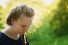 Muchacha bastante adolescente que mira abajo y thining sobre algo en parque Imagenes de archivo