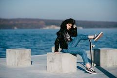 Muchacha bastante adolescente que pasa tiempo en el parque cerca del agua con su patín Fotografía de archivo libre de regalías