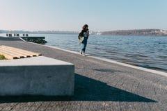 Muchacha bastante adolescente que pasa tiempo en el parque cerca del agua con su patín Imagen de archivo libre de regalías