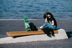Muchacha bastante adolescente que pasa tiempo en el parque cerca del agua con su patín Fotos de archivo
