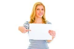 Muchacha bastante adolescente que señala en la hoja del papel en blanco Foto de archivo