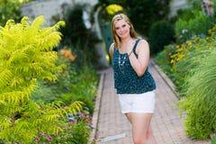 Muchacha bastante adolescente que se coloca en jardines botánicos Fotografía de archivo