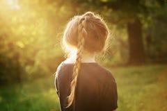 Muchacha bastante adolescente que se coloca y thining sobre algo en parque Fotos de archivo