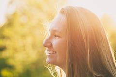 Muchacha bastante adolescente que sonríe en puesta del sol caliente Imagen de archivo