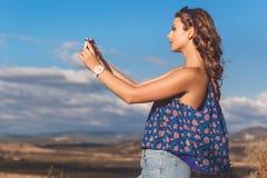 Muchacha bastante adolescente que toma la foto de la naturaleza por el teléfono Fotografía de archivo libre de regalías