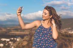 Muchacha bastante adolescente que toma la imagen por el teléfono Imagen de archivo