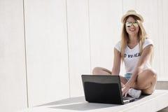 Muchacha bastante adolescente que usa su ordenador portátil en el banco Fotos de archivo