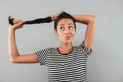 Muchacha bastante asiática que juega con su pelo largo mientras que se coloca Fotografía de archivo