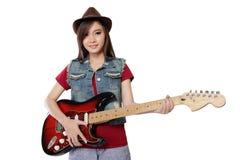 Muchacha bastante asiática que presenta con su guitarra, en el fondo blanco Fotografía de archivo