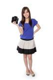 Muchacha bastante asiática que se coloca con la cámara en su mano Fotos de archivo