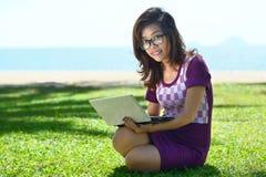 Muchacha bastante asiática que se sienta con un ordenador portátil en el parque en la hierba Fotos de archivo