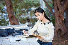 Muchacha bastante asiática que se sienta en la tabla en el parque con un libro a Imagenes de archivo