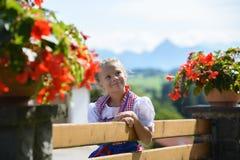 Muchacha bastante bávara con las flores en la granja Montañas en backgrou Fotos de archivo