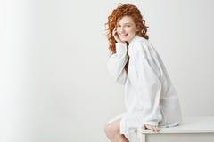Muchacha bastante blanda juguetona con el pelo rojo rizado que ríe planteando sentarse en la tabla sobre el fondo blanco Copie el Fotos de archivo libres de regalías