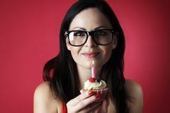 Muchacha bastante caucásica con los vidrios que soplan hacia fuera la vela en su torta de la taza en fondo rojo Fotos de archivo libres de regalías