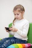 Muchacha bastante caucásica que juega al juego en el teléfono móvil, el sentarse interior Fotografía de archivo