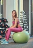 Muchacha bastante deportiva de los jóvenes en la ropa de deportes rosada que se sienta en una bola de la aptitud en el gimnasio Fotografía de archivo libre de regalías