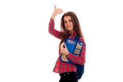 Muchacha bastante elegante del estudiante con la mochila en sus hombros y carpeta para los cuadernos en su presentación de las ma Fotos de archivo