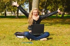 Muchacha bastante emocionada con una computadora portátil Imagen de archivo