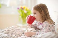 Muchacha bastante enferma del pequeño niño que pone en té de la bebida de la cama Foto de archivo libre de regalías