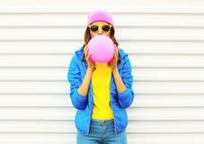Muchacha bastante fresca de la moda del retrato que sopla el balón de aire rosado en la ropa colorida que se divierte sobre el fo Fotos de archivo libres de regalías