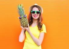Muchacha bastante fresca en gafas de sol con la piña que se divierte sobre colorido Fotografía de archivo