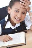 Muchacha bastante joven de la escuela que lee un libro Foto de archivo libre de regalías