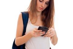 Muchacha bastante joven de los estudiantes con la mochila azul en hombro y el teléfono móvil en la presentación de las manos aisl Fotos de archivo libres de regalías