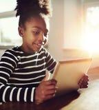 Muchacha bastante negra que juega en la tableta Imágenes de archivo libres de regalías