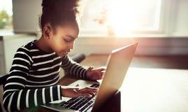 Muchacha bastante negra que mecanografía en el teclado de su ordenador portátil Fotos de archivo