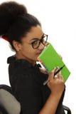 Muchacha bastante negra que se sienta en una silla de la oficina con un cuaderno y Imagen de archivo