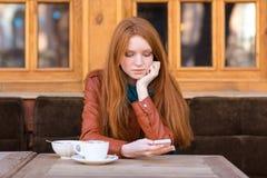 Muchacha bastante pensativa con el café de consumición del pelo rojo al aire libre Foto de archivo libre de regalías