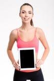 Muchacha bastante positiva de la aptitud que sostiene la pantalla de tableta en blanco Foto de archivo libre de regalías